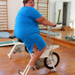 Overweight woman exercising on bike - Stock Photo