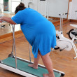 Overweight woman running on trainer treadmill — Stock Photo #7368386