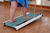Overweight woman legs on trainer treadmill — Stock Photo
