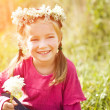 Little girl in wreath of flowers - Stok fotoğraf
