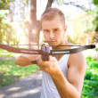 Strong young men with arbalest - Stock Photo