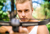 Strong young men with arbalest — Stock Photo
