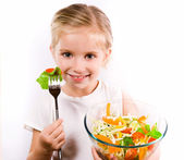Little girl eating vegetable salad — Stok fotoğraf