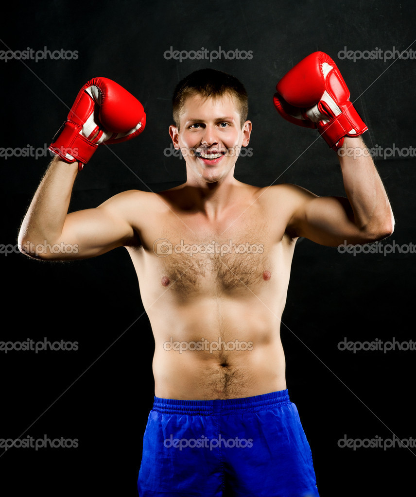 Portrait of young man with boxing  gloves over black background — Stock Photo #7144874