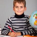 Cute schoolboy is writting — Stock Photo