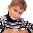 Cute schoolboy is writting - Stockfoto