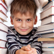 Schoolboy and a heap of books isolated on a white background - Стоковая фотография