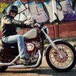 Biker man sits on a bike - Stock Photo