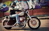 Biker man sits on a bike — Foto Stock