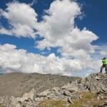 Girl-tourist photographs in mountains — Stock Photo