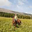 Stock Photo: Girl on a meadow astride a horse