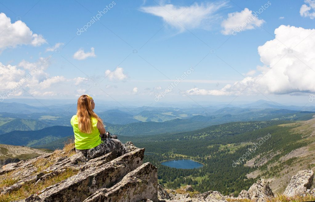 Girl sits on a rock and looks at mountain lake — Stock Photo #6835801