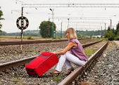 Girl on railway sitting with red suitcase — Stock Photo