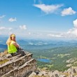 Emale tourist resting at mountain peak - Stock Photo