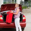 Girl stacks a suitcase in a car luggage carrier — Stockfoto