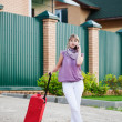 Girl with a suitcase calls a taxi by a mobile phone — Stock Photo