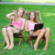 Two girls have a rest on a green glade — Stock Photo