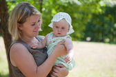 Young mum walks with the child in city park — Stock Photo