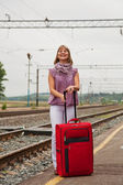Woman with a red suitcase standing on the railway station — Stock Photo