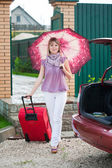Happy woman with luggage go to car — Stock Photo
