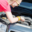 Stock Photo: Blonde woman trying to fix the car