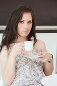 Girl drinks coffee in cafe — Foto de Stock