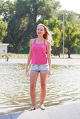 Girl in a pink vest and shorts costs on a fountain side — Stock Photo