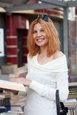 Fille sélectionne le livre dans la boutique de la rue — Photo