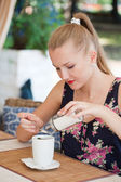 Girl puts sugar in a cup with tea — Stock Photo
