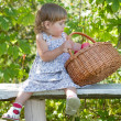 Little girl sits on a bench with a basket of apples - Stock Photo