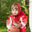 Little girl in Russian traditional dress standing next to a birch and holds — Stock Photo #7250102