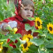 Little girl in Russian national dress among sunflowers — Stock Photo