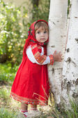 Little girl in Russian traditional dress standing next to a birch — Stock Photo