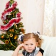 Little girl at a Christmas fir-tree. — Stock Photo #7354571