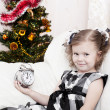 Little girl looks at alarm clock in expectation of Christmas approach — Stock Photo #7354577