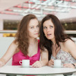 Two girls sitting in cafe in shopping center — Stock Photo