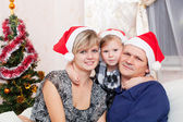 Family with a small daughter in expectation of Christmas — Stock Photo