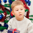 Little boy sits with a gift near the dressed up New Year tree - Stock Photo