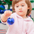 Little girl sits near the dressed up New Year tree — Stock Photo #7375809