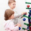 Brother and sister dress up New Year tree — Stock Photo #7375810
