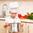 Little boy on kitchen helps to make a dinner — Stock Photo