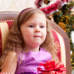 Little girl at a Christmas fir-tree. — Stock Photo #7403592