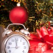Soon new year! Hours and a gift stand under a fir-tree — Stock Photo