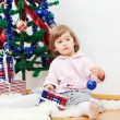 Little girl at a Christmas fir-tree. — Stockfoto