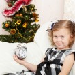 Little girl looks at an alarm clock in expectation of Christmas approach - Stock Photo