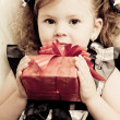 Little girl with a red gift box in hands — Stock Photo