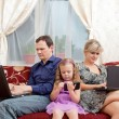 Family sits on a sofa everyone about the the computer. — Stock Photo