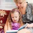 Mum reads to the small daughter the book — Stock Photo