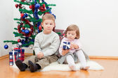 Small children sit at a New Year tree — Stock Photo
