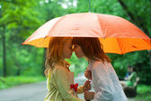 Children under an umbrella in park in the rain — Stock Photo